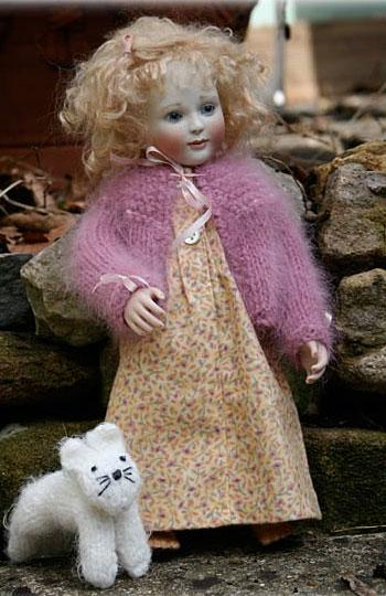 "For any of our small, 10"" - 11 1/2"" wood bodied dolls. The outfit is shown here on Kitty.  A bedtime set of cotton flannel nightie and angora bed-jacket, also included in this set a delightful little white knitted Kitty."